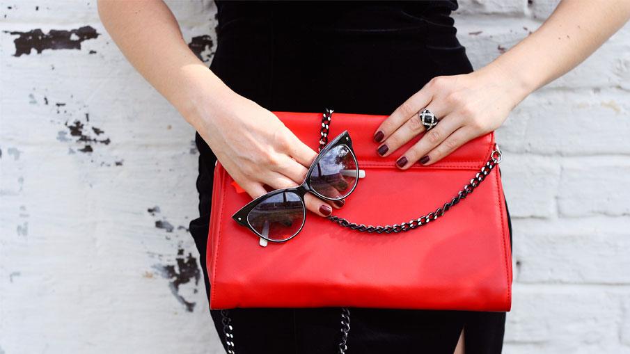 mulher usando vestido preto combinando com bolsa de couro vermelho, óculos de sol e anel semijoia