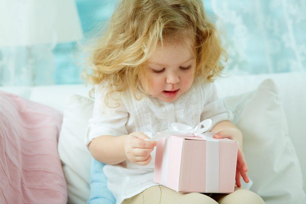criança abrindo uma caixa de presente rosa com fita branca