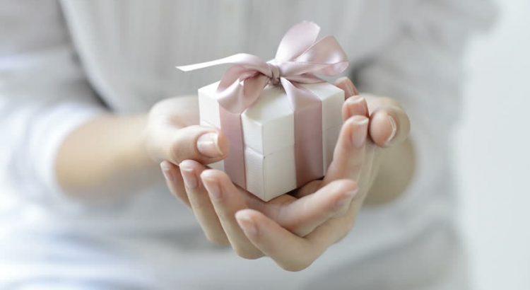 mulher segurando uma pequena caixa de presente branca com fita rosa