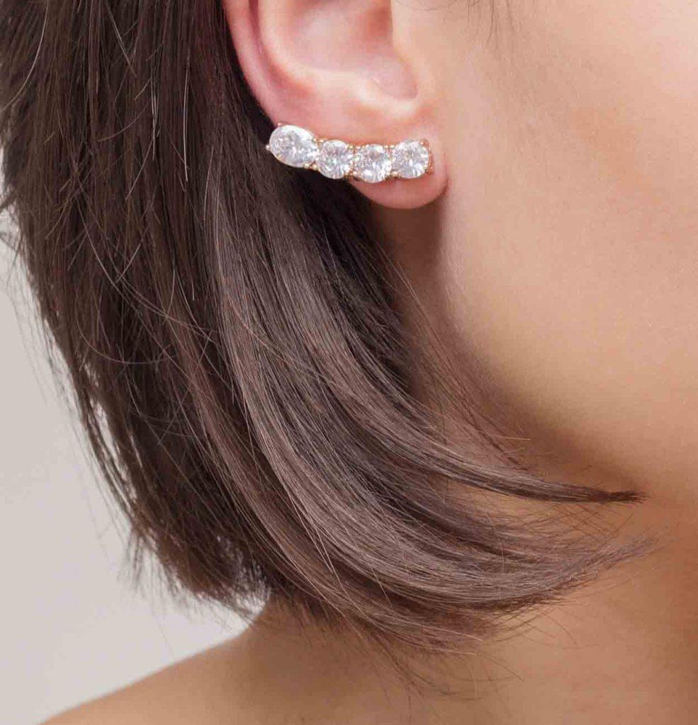 Modelo usando um brinco ear cuf dourado com pedras cristal semijoia