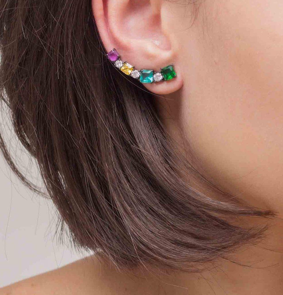 Imagem de modelo usando um brinco ear cuff com pedras coloridas em ródio negro semijoia