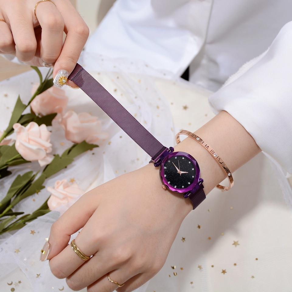 Imagem de um relógio de pulso roxo feminino no braço mostrando sua pulseira esteira magnética