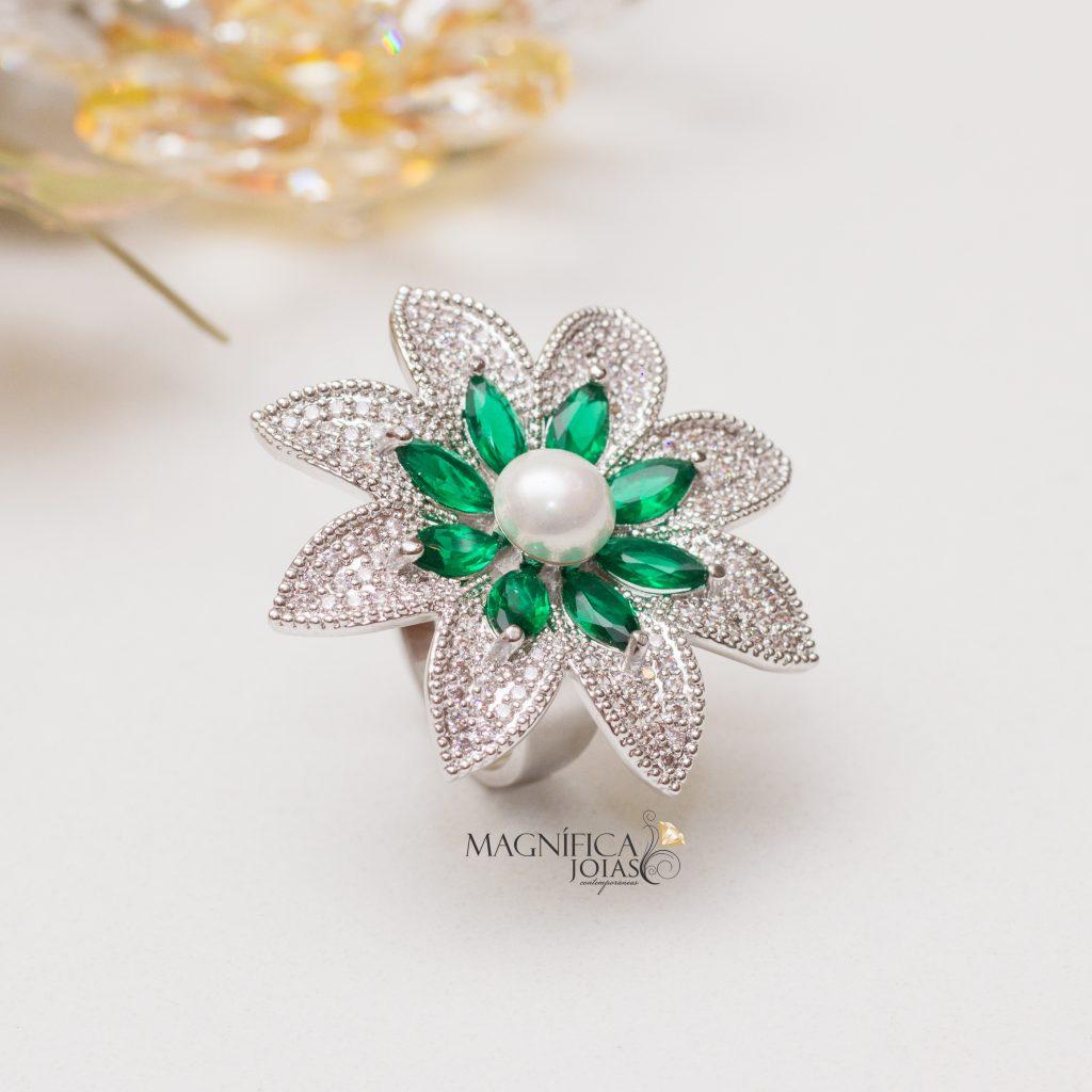 Imagem com fundo branco e anel de ródio em formato de flor cravejado com zircônias e esmeraldas semijoia