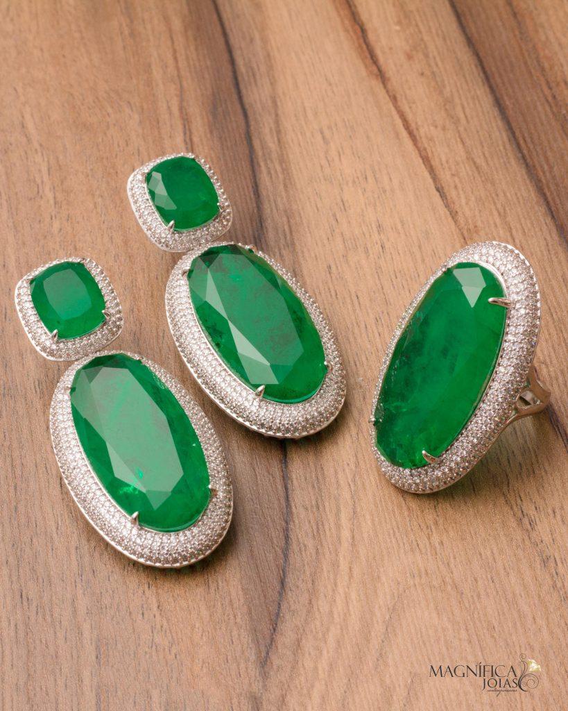 Imagem com fundo em madeira de anel e brinco em ródio branco com pedra esmeralda fusion cravejados com zircônias semijoia