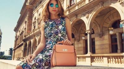 mulher com vestido estampado combinando com bolsa bege e óculos de sol